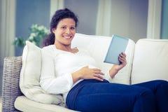 Портрет счастливой женщины возлежа на софе с таблеткой Стоковые Изображения