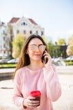 Портрет счастливой женщины говоря на телефоне и выпивая кофе Стоковая Фотография