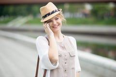 Портрет счастливой женщины говоря на smartphone пока идущ Стоковое фото RF