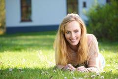 Портрет счастливой женщины лежа на траве outdoors Стоковое Изображение RF