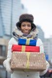 Портрет счастливой женщины нося штабелированные подарки во время зимы Стоковые Изображения