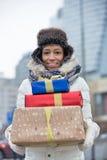 Портрет счастливой женщины нося штабелированные подарки во время зимы Стоковое фото RF