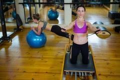 Портрет счастливой женщины практикуя протягивающ тренировку на реформаторе Стоковая Фотография RF