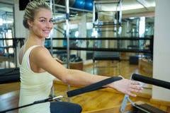 Портрет счастливой женщины практикуя протягивающ тренировку на реформаторе Стоковое Изображение