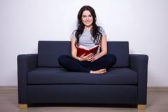 Портрет счастливой женщины сидя на софе и книге чтения Стоковое Фото
