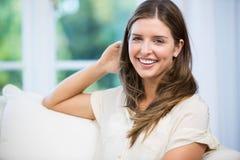 Портрет счастливой женщины сидя на софе Стоковые Изображения RF