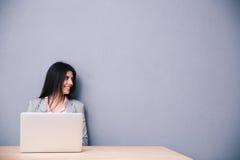 Портрет счастливой женщины сидя на таблице с компьтер-книжкой Стоковое Фото