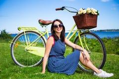 Портрет счастливой женщины сидя на траве с винтажным bicycl Стоковые Изображения