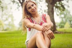 Портрет счастливой женщины сидя на траве Стоковые Изображения RF