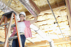 Портрет счастливой женщины стоя на лестнице работая на незаконченном потолке Стоковые Фотографии RF