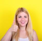 Портрет счастливой женщины с большими пальцами руки вверх против желтой предпосылки Стоковое Изображение RF
