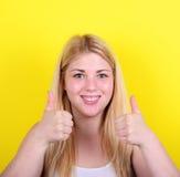 Портрет счастливой женщины с большими пальцами руки вверх против желтой предпосылки Стоковая Фотография RF