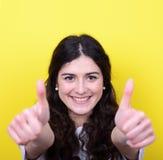 Портрет счастливой женщины с большими пальцами руки вверх против желтой предпосылки Стоковые Фотографии RF