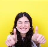 Портрет счастливой женщины с большими пальцами руки вверх против желтой предпосылки Стоковое фото RF