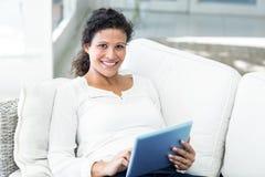Портрет счастливой женщины с таблеткой на софе Стоковые Фотографии RF