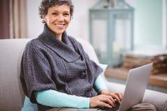 Портрет счастливой зрелой женщины используя компьтер-книжку Стоковая Фотография
