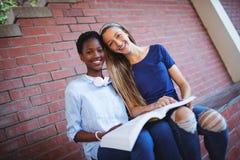 Портрет счастливой книги чтения школьниц Стоковые Фото