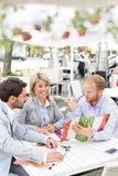 Портрет счастливой коммерсантки при мужские коллеги решая меню на кафе тротуара Стоковая Фотография RF