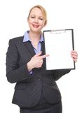 Портрет счастливой коммерсантки указывая к пустой доске сзажимом для бумаги знака Стоковая Фотография RF