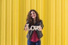 Портрет счастливой красивой молодой женщины держа ove слова ВЛЮБЛЕННОСТИ Стоковые Изображения