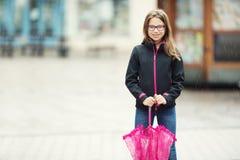 Портрет счастливой красивой молодой пре-предназначенной для подростков девушки с розовым зонтиком под дождем Стоковое Изображение