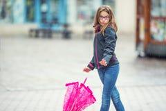 Портрет счастливой красивой молодой пре-предназначенной для подростков девушки с розовым зонтиком под дождем Стоковая Фотография