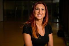Портрет счастливой красной с волосами женщины представляя пока ослабляющ в спортзале Стоковые Изображения