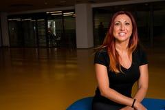 Портрет счастливой красной с волосами женщины представляя пока ослабляющ в спортзале Стоковая Фотография RF