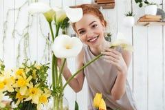 Портрет счастливой молодой дамы смотря из белых цветков пока работающ Стоковая Фотография RF