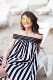 Портрет счастливой молодой женщины брюнет в черно-белом striped платье сидя на sunbed пока ослабляющ на пляже Стоковая Фотография RF