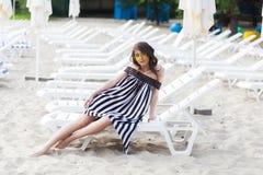 Портрет счастливой молодой женщины брюнет в черно-белом striped платье сидя на sunbed пока ослабляющ на пляже Стоковые Фото