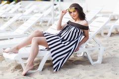 Портрет счастливой молодой женщины брюнет в черно-белом striped платье сидя на sunbed пока ослабляющ на пляже Стоковое Изображение RF