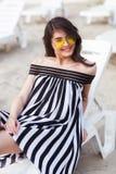 Портрет счастливой молодой женщины брюнет в черно-белом striped платье сидя на sunbed пока ослабляющ на пляже Стоковая Фотография