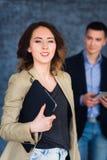 Портрет счастливой молодой женщины держа компьтер-книжку и смотря камеру Стоковое Изображение RF