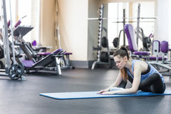 Портрет счастливой молодой женщины делая протягивающ тренировку в спортзале Стоковое фото RF