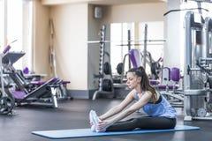 Портрет счастливой молодой женщины делая протягивающ тренировку в спортзале Стоковые Изображения RF