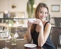 Портрет счастливой молодой женщины имея кофе на ресторане Стоковые Изображения