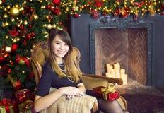 Портрет счастливой молодой женщины около рождественской елки Стоковое Изображение