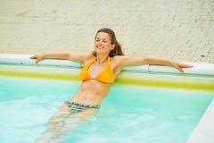 Портрет счастливой молодой женщины ослабляя в бассейне Стоковая Фотография RF