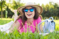 Портрет счастливой молодой женщины при шляпа и солнечные очки лежа в парке на пикнике Стоковые Фотографии RF