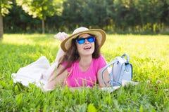 Портрет счастливой молодой женщины при шляпа и солнечные очки лежа в парке на пикнике Стоковые Изображения