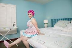 Портрет счастливой молодой женщины сидя на кровати с утюжа доской в предпосылке Стоковые Изображения