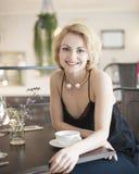 Портрет счастливой молодой женщины сидя на таблице ресторана Стоковая Фотография