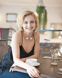 Портрет счастливой молодой женщины сидя на таблице ресторана Стоковые Фотографии RF