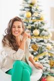 Портрет счастливой молодой женщины сидя около рождественской елки Стоковое Изображение