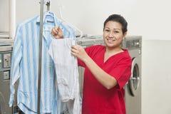Портрет счастливой молодой женщины с смертной казнью через повешение рубашки в Laundromat стоковое фото