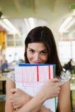 Портрет счастливой молодой коммерсантки с книгами в офисе Стоковые Фото