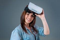 Портрет счастливой молодой красивой девушки получая опыт используя стекла VR-шлемофона виртуальной реальности Стоковое фото RF