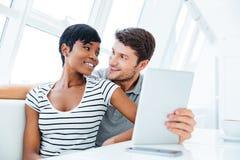 Портрет счастливой пары используя планшет в ресторане Стоковые Фото