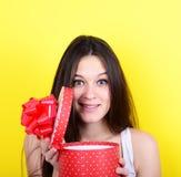 Портрет счастливой подарочной коробки отверстия женщины против желтого backgrou Стоковое Фото